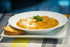 Minestrone Soup: traditional Italian thick vegetable soup served with pesto And a slice of sourdough bread