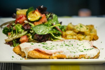 Pollo Alla Valdostana: chicken schnitzel topped with ham and melted cheese Served with roasted potato and salad